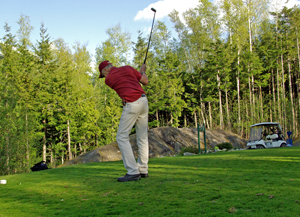 golfer swinging at skeena golf course